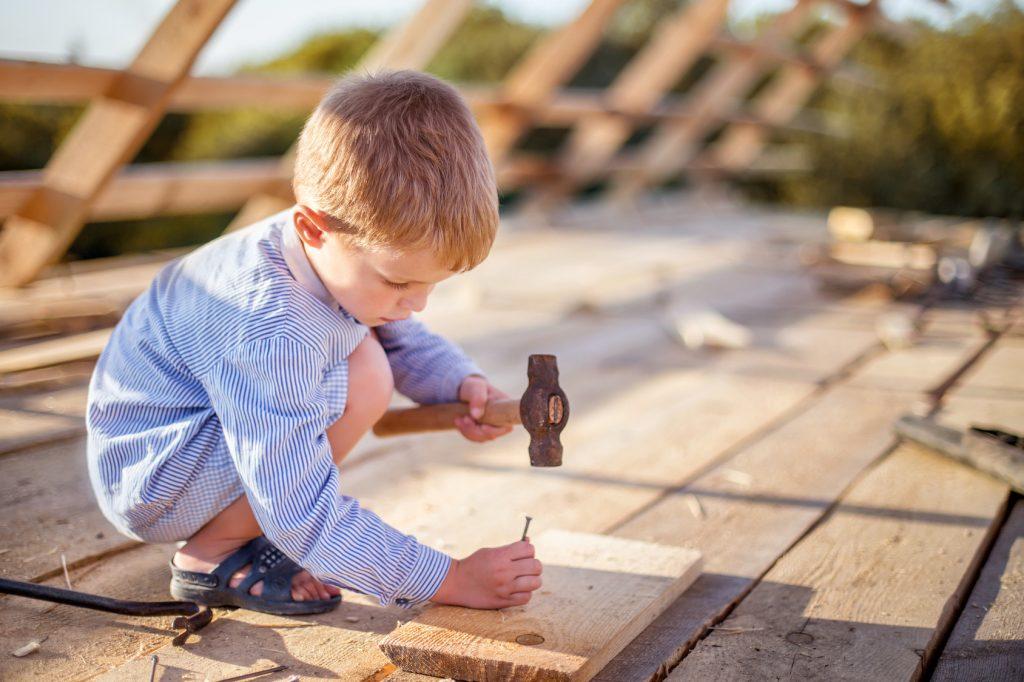 Kind hammert mit Hammer Nägel in Holz
