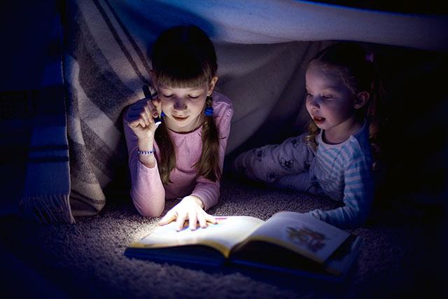 Kinder lesen und erzählen eine Geschichte auf einer Übernachtungsparty